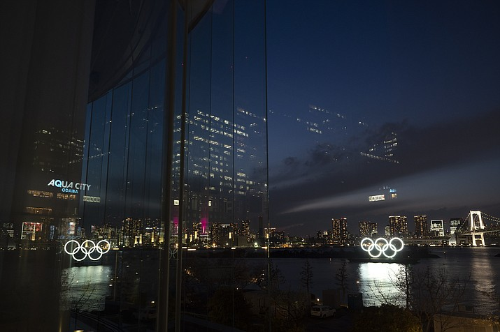 The Olympic rings are reflected in the glass wall of a wedding chapel in the Odaiba section of Tokyo, Monday, March 23, 2020. The Tokyo Olympics are going to happen — but almost surely in 2021 rather than in four months as planned. (Jae C. Hong/AP)