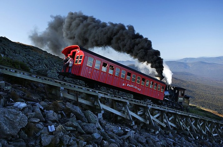 In this Sept. 24, 2017, file photo, a vintage coal-fired steam engine pushes a passenger car up the Cog Railway on a 3.8-mile journey to the summit of 6,288-foot Mount Washington in New Hampshire. A hiker descending Mount Washington on Sunday, March 22, 2020, who fell about 200 feet and was injured, was rescued with the help of the Cog Railway. (AP Photo/Robert F. Bukaty)