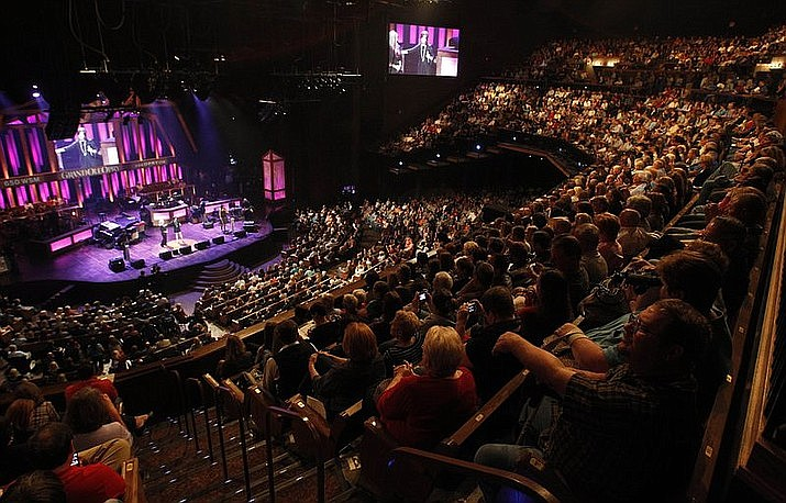 In this Sept. 28, 2010, file photo, country music fans watch a performance during a broadcast of the Grand Ole Opry in Nashville, Tenn. The Opry is playing on through the coronavirus spread. The country music institution, which has been airing Saturday nights for 94 years, is set to broadcast live on television this Saturday from a mostly empty venue. (AP Photo/Mark Humphrey)