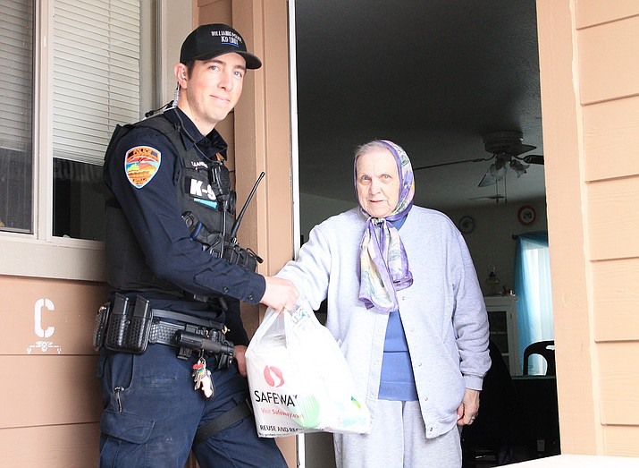 Officer Thomas Sanders with Williams Police Department brings Alayne Newbold supplies March 20. The department is offering to supply food and other necessities to senior citizens. (Loretta McKenney/WGCN)