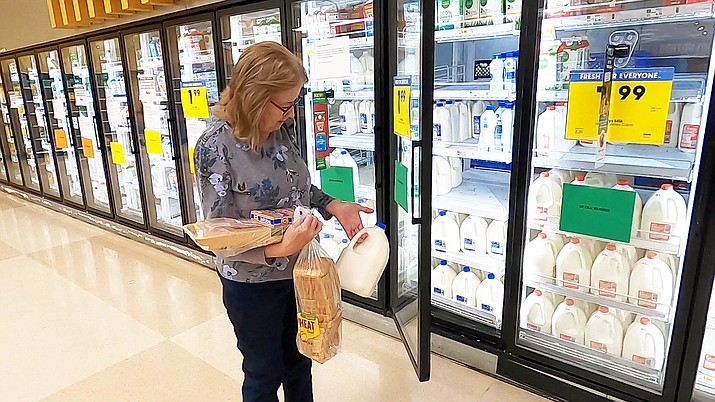 Margaret Conway pulls a gallon of milk from a fully-stocked refrigerator at a local grocer on Tuesday, March 24. During the COVID-19 pandemic, seniors are receiving special morning hours to do their shopping at some grocers and big-box stores. (Jesse Bertel/Courier)