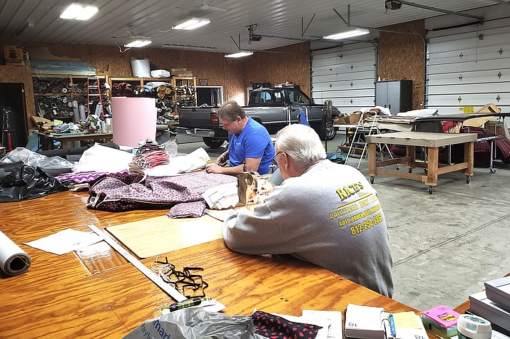Bill Purdue, left, cuts pieces of fabric while Mike Rice sews them into face masks in Rice's Autobody and Upholstery Shop in Washington, Ind. Purdue and Rice will deliver the masks this week to Deaconess Health System in Evansville, Indiana, which asked community members to sew cloth masks for health care workers who may face a shortage amid the coronavirus pandemic. They're among legions of everyday Americans making face masks for desperate hospitals, nursing homes and homeless shelters that could run out of personal protective equipment.(photo courtesy of Robin Rice via AP)