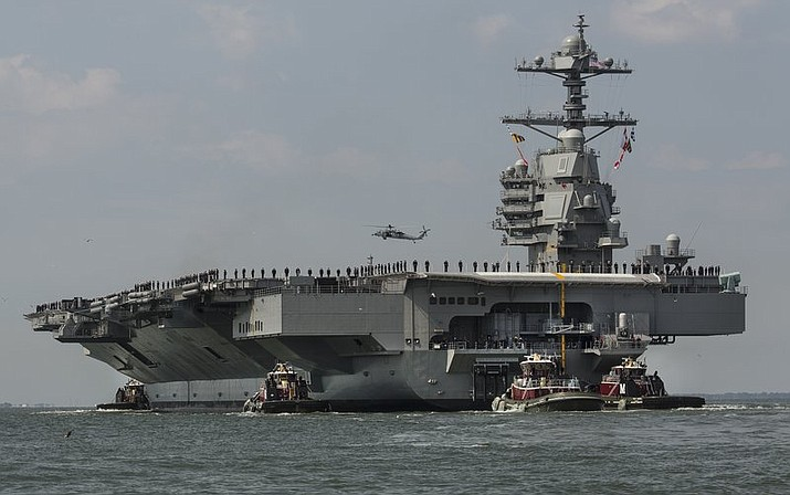 In this April 14, 2017 file photo, as crew members stand on the deck, the aircraft carrier USS Gerald R. Ford heads to the Norfolk, Va., naval station. Toilets on the USS Gerald R. Ford and USS George H.W. Bush carriers that have become repeatedly clogged could require treatments costing $400,000 each to get them working properly, a U.S. Government Accountability Office report found. (Bill Tiernan/The Virginian-Pilot via AP)