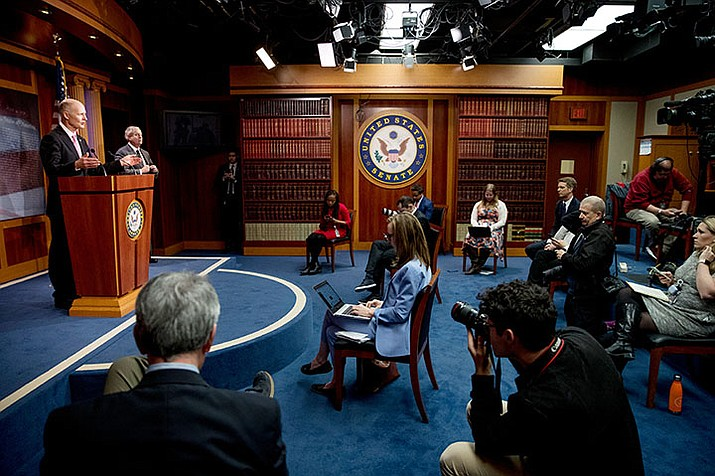 "Sen. Rick Scott, R-Fla., left, accompanied by Sen. Lindsey Graham, R-S.C., second from left, speaks at a news conference about the coronavirus relief bill on Capitol Hill in Washington, Wednesday, March 25, 2020. Senators discussed what they are calling a ""drafting error"" in the 2 trillion dollar stimulus bill expected to be voted on later in the day in the Senate. (Andrew Harnik/AP)"