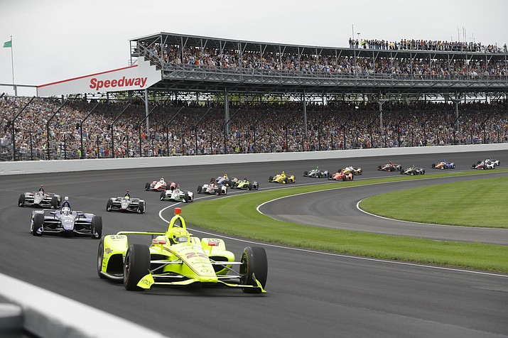 In this May 26, 2019, photo, Simon Pagenaud, of France, leads the field through the first turn on the start of the Indianapolis 500 IndyCar at Indianapolis Motor Speedway, in Indianapolis. The Indianapolis 500 scheduled for May 24 has been postponed until August because of the coronavirus pandemic and won't run on Memorial Day weekend for the first time since 1946.  The race will instead be held Aug. 23. (Darron Cummings/AP, file)