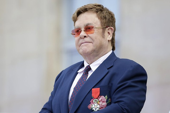 """This June 21, 2019 file photo shows Elton John at a ceremony honoring him with the Legion of Honor in Paris. John is hosting a """"living room"""" concert aimed at bolstering American spirits during the coronavirus crisis and saluting those countering it. The event was announced Wednesday by iHeartMedia and Fox. Alicia Keys, Billie Eilish, Mariah Carey, the Backstreet Boys, Tim McGraw and Billie Joe Armstrong are scheduled to take part in the concert airing at 9-10 p.m. Eastern Sunday on Fox TV and on iHeartMedia radio stations. (AP Photo/Lewis Joly, Pool)"""