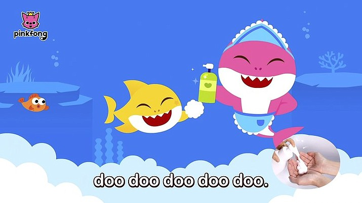 """This image released by Pinkfong shows. scene from the modified """"Baby Shark"""" video, reworked to teach kids good hygiene to combat COVID-19. The company has debuted the """"Wash Your Hands With Baby Shark"""" video and now has started a dance challenge to encourage families to upload videos of their children washing hands to the song. (Pinkfong via AP)"""