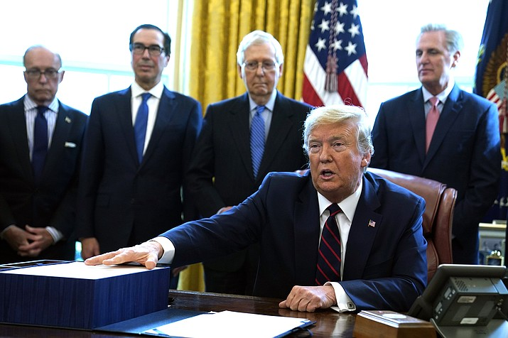 President Donald Trump speaks before he signs the coronavirus stimulus relief package in the Oval Office at the White House March 27, in Washington. Listening are from left, Larry Kudlow, White House chief economic adviser, Treasury Secretary Steven Mnuchin, Senate Majority Leader Mitch McConnell, R-Ky., and House Minority Leader Kevin McCarty of Calif. (AP Photo/Evan Vucci)
