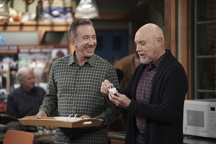 "Tim Allen, left, and Hector Elizondo in a scene from the comedy series ""Last Man Standing,"" that aired on Thursday, March 19, 2020. With millions of people stuck at home due to the coronavirus outbreak, television viewership is on the rise. Broadcast networks see their 8 p.m. shows doing well in part, they suspect, because many are being shown after expanded local news. Fox's ""Last Man Standing"" last week, for example, was up 50 percent in live viewing, Nielsen said. (Michael Becker/Fox via AP)"