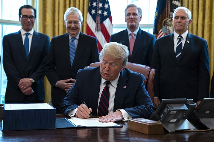 In this March 27, 2020 photo, President Donald Trump signs the coronavirus stimulus relief package in the Oval Office at the White House in Washington, as Treasury Secretary Steven Mnuchin, Senate Majority Leader Mitch McConnell, R-Ky., House Minority Leader Kevin McCarty, R-Calif., and Vice President Mike Pence watch. Payments from a federal coronavirus relief package could take several weeks to arrive. While you wait, prep your finances and make a plan for using any money you receive. (Evan Vucci/AP, File)