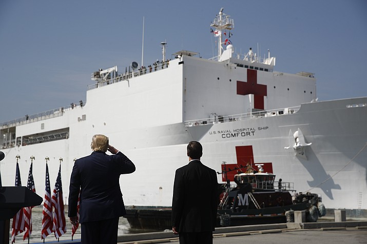 President Donald Trump salutes as the U.S. Navy hospital ship USNS Comfort pulls away from the pier at Naval Station Norfolk in Norfolk, Va., Saturday, March 28, 2020. The ship is departing for New York to assist hospitals responding to the coronavirus outbreak. Defense Secretary Mark Esper is at right. (Patrick Semansky/AP)