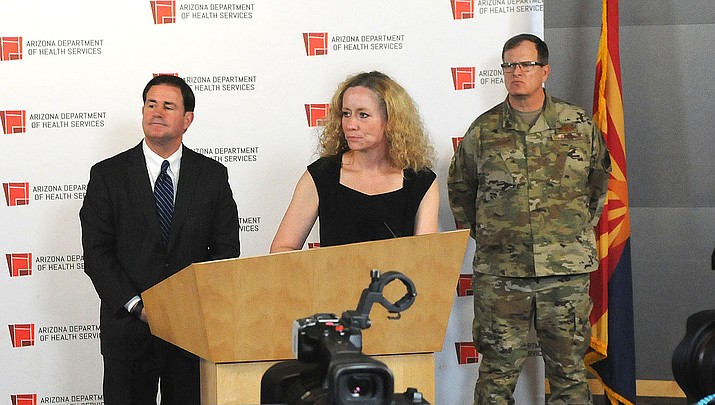 """Arizona Gov. Doug Ducey, left, watches as state Health Director Cara Christ talks to the media last week. Ducey's extensive list of """"essential"""" businesses that can't be closed have tied the hands of some local governments that are hoping to enact more restrictive provisions in light of the coronavirus pandemic. (Photo by Howard Fischer/For the Miner)"""