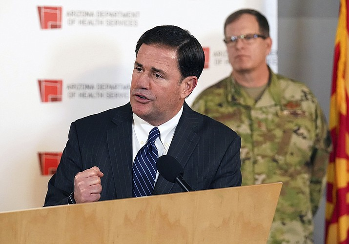 Arizona Governor Doug Ducey, with Michael T. McGuire, Adjutant General for Arizona and Director of the Arizona Department of Emergency and Military Affairs holds a press conference to update Arizona's preparedness for COVID-19 coronavirus outbreak at the Arizona State Public Health Laboratory Wednesday, March 25, 2020 in Phoenix. (Rob Schumacher/The Arizona Republic via AP, Pool)
