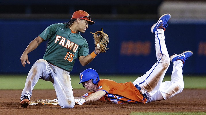 In this March 4, 2020, file photo, Florida's Brock Edge, right, steals second base, beating the tag by Florida A&M infielder Octavien Moyer (15), during the eighth inning of an NCAA college baseball game in Gainesville, Fla. The NCAA is planning on extending the eligibility of athletes on spring sports teams one year to make up for the season lost to the new coronavirus. The details of how this will work are still being ironed out. (Gary McCullough/AP, file)