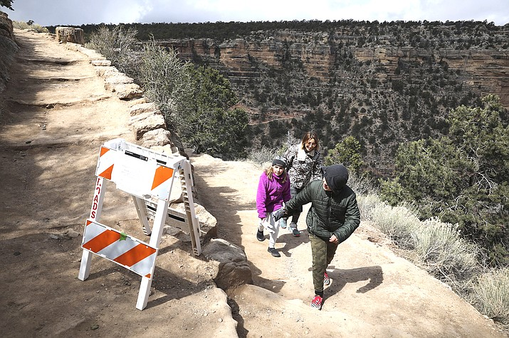 Shelly Clayton, center, walks up the Bright Angel Trail at Grand Canyon National Park, Ariz., with her children Audrey Kuhar, 11, left, and Cooper Kuhar, 11. The park has closed restaurants, lodges, visitor centers, campgrounds and other services as it awaits approval from the federal government for a full shutdown. (Jake Bacon/Arizona Daily Sun via AP)