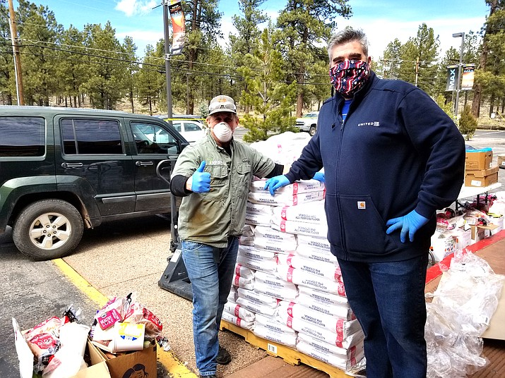 Stoney Ward (left) of Buck Wild Hummer Tours and Tusayan Vice Mayor Brady Harris help with Tusayan Food Bank supplies  March 25 in response to an increase in demand due to COVID-19. (Lo Frisby/WGCN)