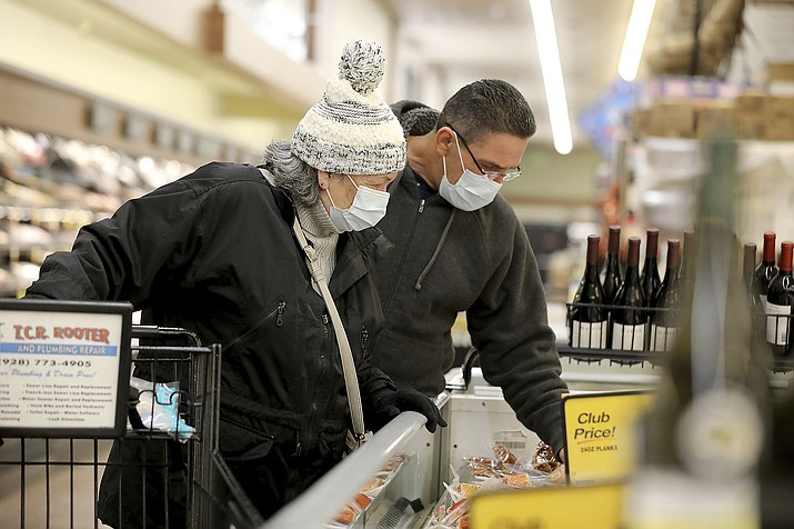 Hector Molina, right, helps his mother Gertrude Moore as the pair shop at the Safeway store in the University Plaza shopping center in Flagstaff, Ariz., at 6 a.m. Thursday morning, April 2, 2020. Some area stores have set aside special hours for seniors to shop to avoid exposure to the general public. (Jake Bacon/Arizona Daily Sun via AP)