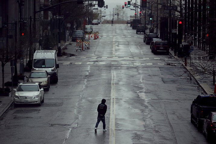 In this April 3, 2020, file photo a man crosses an empty street in downtown Kansas City, Mo. Americans are increasingly taking preventative measures, including staying away from large crowds and avoiding touching their hands to their faces, amid growing fears of infection with COVID-19, a new poll from The Associated Press-NORC Center for Public Affairs Research found. (AP Photo/Charlie Riedel, File)