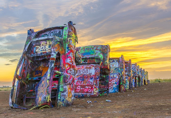 The sun rises and illuminates the vibrant colors of the vehicles at Cadillac Ranch, one of most famous roadside attractions on Route 66 - where 10 mid-20th Century Cadillacs are half buried in a farm field in Amarillo, Texas. Photo by Efren Lopez
