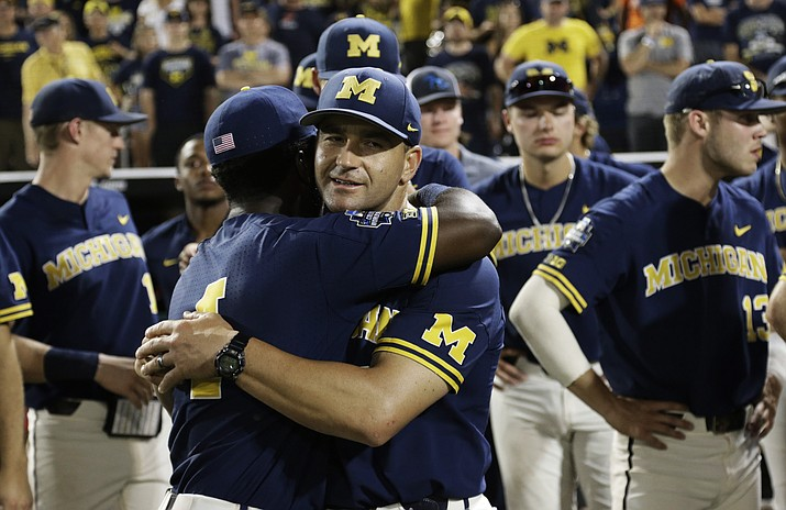 """In this June 26, 2019, file photo, Michigan coach Erik Bakich, center, is hugged by Michigan's Ako Thomas (4) as they watch Vanderbilt celebrate after Vanderbilt defeated Michigan to win Game 3 of the NCAA College World Series baseball finals in Omaha, Neb. As disappointing as it's been to have the college baseball season shut down because of the coronavirus pandemic, Michigan coach Erik Bakich sees a silver lining. """"I do think the coming years will be the deepest college baseball has ever been,"""" he said. (Nati Harnik/AP, file)"""