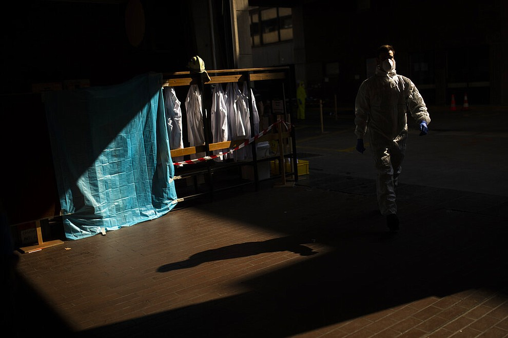 A firefighter, wearing full protective equipment, leaves to pick up a coronavirus patient in Brussels, Thursday, April 9, 2020. The new coronavirus causes mild or moderate symptoms for most people, but for some, especially older adults and people with existing health problems, it can cause more severe illness or death. (AP Photo/Francisco Seco)