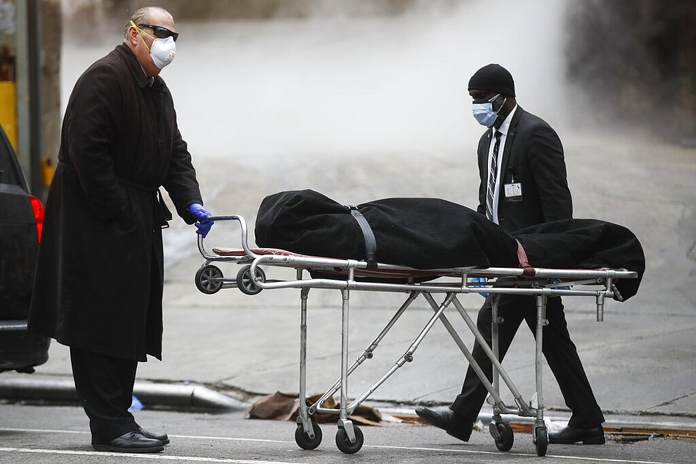 A funeral director wears personal protective equipment due to COVID-19 concerns while collecting a body at The Brooklyn Hospital Center, Thursday, April 9, 2020, in the Brooklyn borough of New York. New York state posted a record-breaking number of coronavirus deaths for a third consecutive day even as a surge of patients in overwhelmed hospitals slowed, while isolation-weary residents were warned Thursday the crisis was far from over. (AP Photo/John Minchillo)