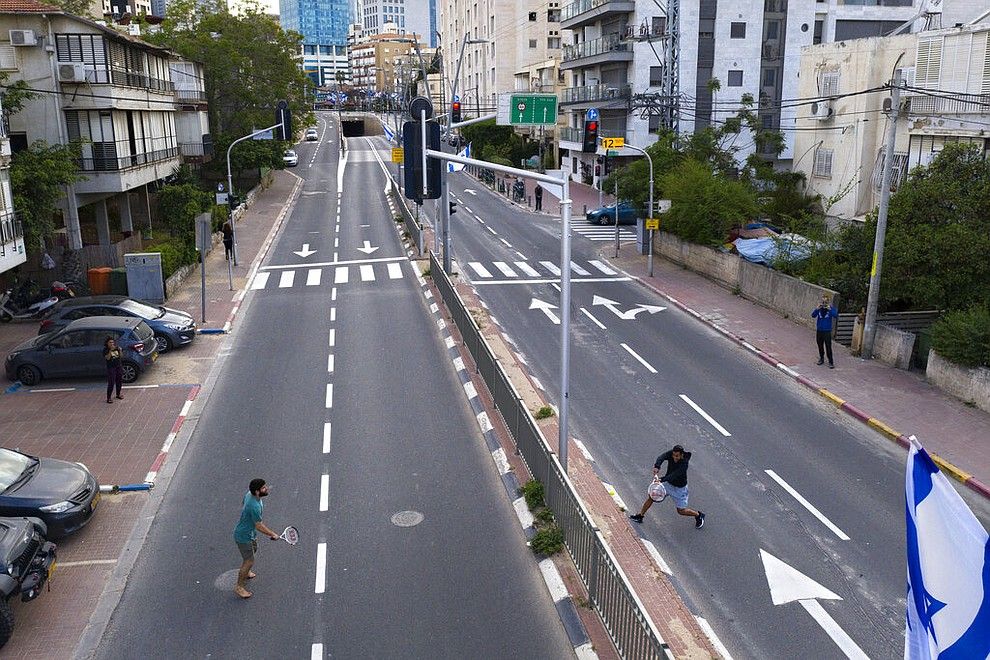 Israelis play tennis on an empty road during lockdown following the government's measures to help stop the spread of the coronavirus, in Ramat Gan, near Tel Aviv, Israel, Thursday, April 9, 2020. (AP Photo/Oded Balilty)