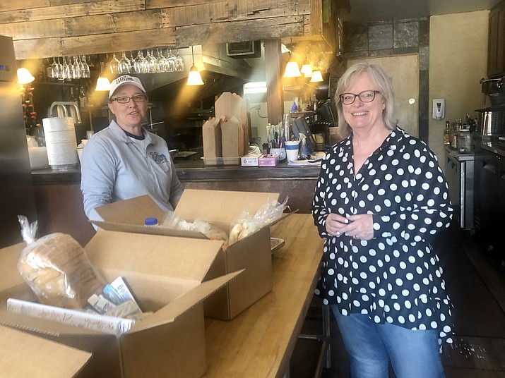El Gato Azul staffer Sarah Decker works to fill food boxes for the restaurant's Gato Community Cares program Wednesday, April 8, 2020, while Allan's Flowers owner Rakini Chinery awaits the boxes for delivery, which the flower shop is providing. (Cindy Barks/Courier)