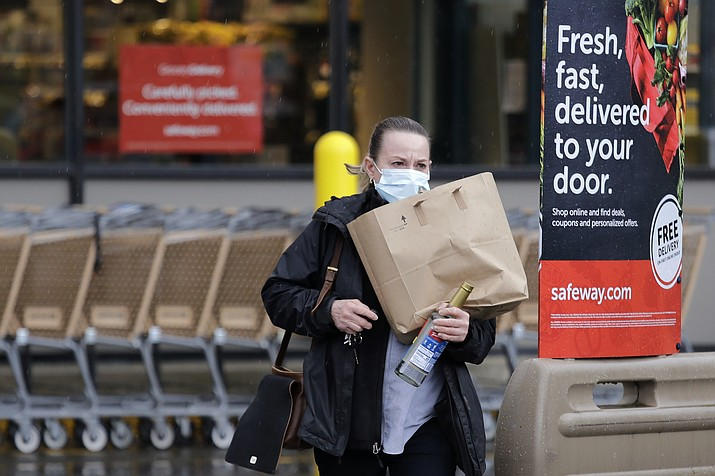 In this Monday, March 30, 2020, photo, a shopper leaves a grocery story with food packed in a paper bag, where the dime-per-bag fee has been waved during the coronavirus outbreak, in Seattle. Just weeks earlier, cities and even states across the U.S. were busy banning straws, limiting takeout containers and mandating that shoppers bring reusable bags or pay a small fee. Grocery clerks are nervous that the virus could linger on reusable fabric bags and their unions are backing them up with demands to end plastic bag fees and suspend bag bans. The plastics industry has seized the moment, lobbying to overturn existing bans on single-use plastics. (Elaine Thompson/AP)