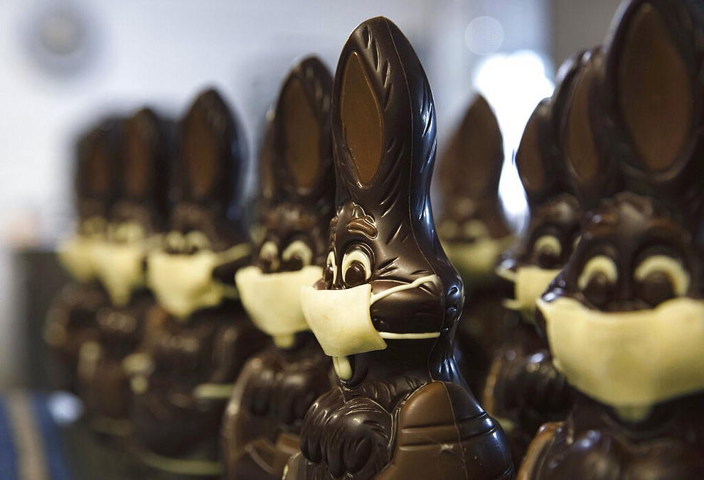 In this photo taken on Wednesday, April 8, 2020, chocolate rabbits with face masks are lined up at the Cocoatree chocolate shop in Lonzee, Belgium. As all non-essential shops in Belgium have been closed due to the outbreak of COVID-19, many chocolatiers have had to resort to online sales, home delivery or pick up on site. The new coronavirus causes mild or moderate symptoms for most people, but for some, especially older adults and people with existing health problems, it can cause more severe illness or death. (AP Photo/Virginia Mayo)