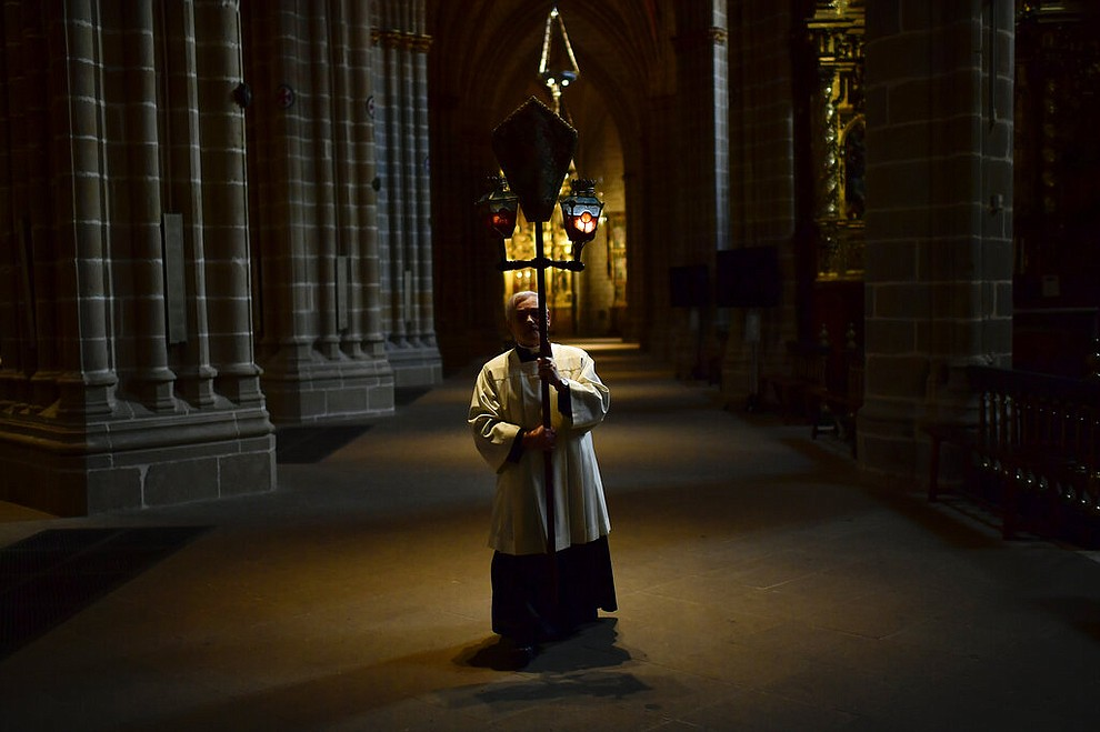 A priest walks during a Stations of the Cross, in an empty Santa Maria Cathedral during Good Friday after celebrations and services were cancelled due to the outbreak of coronavirus, in Pamplona, northern Spain, Friday, April 10, 2020. COVID-19 causes mild or moderate symptoms for most people, but for some, especially older adults and people with existing health problems, it can cause more severe illness or death. (AP Photo/Alvaro Barrientos)