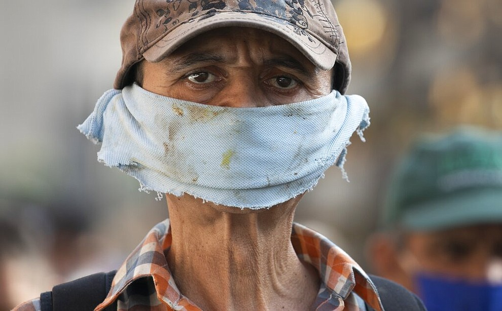 A man wears a piece of cloth as a face mask to avoid spread of the new coronavirus at a street market in Caracas, Venezuela, Friday, April 10, 2020. (AP Photo/Ariana Cubillos)