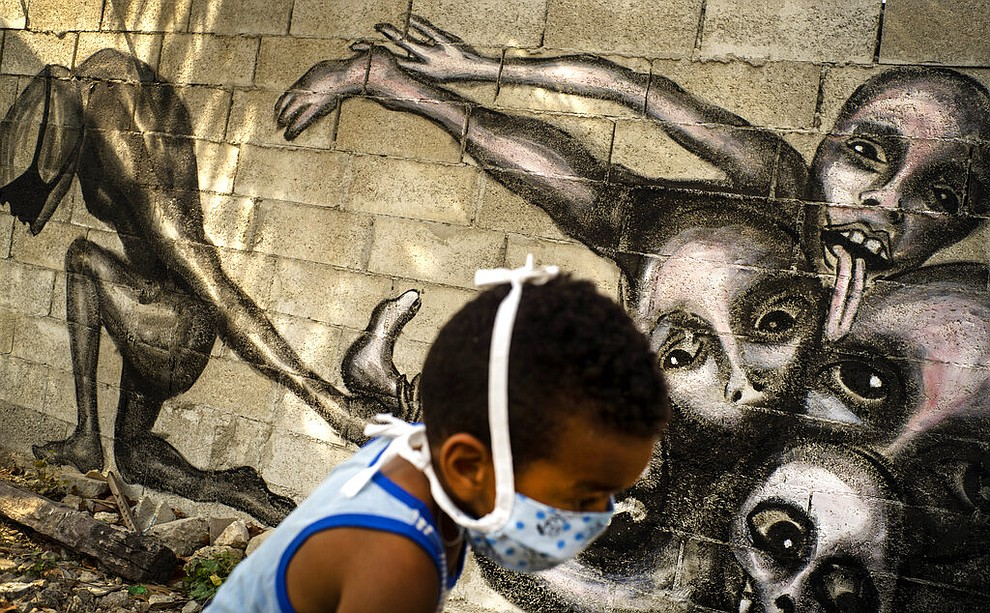 "A boy wearing a mask as a precaution against the spread of the new coronavirus plays in front of a mural by artist Yuriel Pena titled ""Marcha Hacia la Oscuridad,"" or Move Toward Darkness, in the patio of a home in Havana, Cuba, Friday, April 10, 2020. Pena said his latest murals show humanity's powerlessness against the COVID-19 disease. (AP Photo/Ramon Espinosa)"