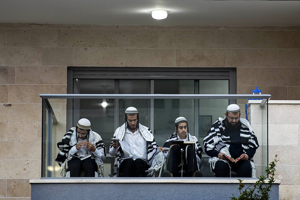 A Jewish family prays on the balcony of their apartment during a lockdown aimed to stop the spread of the coronavirus, in the costal city of Ashkelon, Israel, Friday, April 10, 2020. (AP Photo/Tsafrir Abayov)