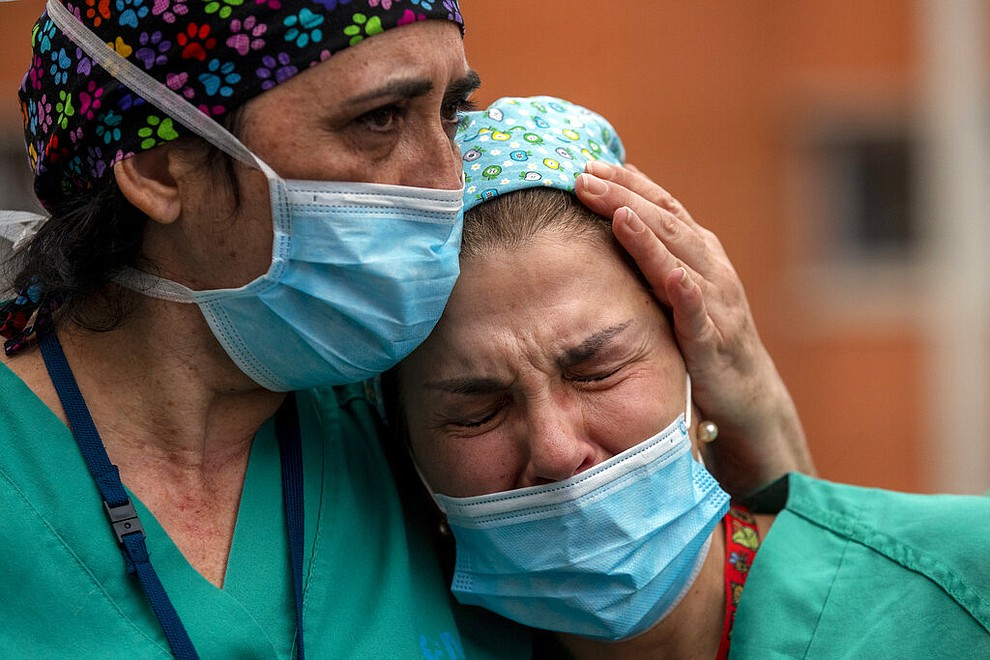 Health workers cry during a memorial for their co-worker Esteban, a male nurse that died of the coronavirus disease, at the Severo Ochoa Hospital in Leganes in Leganes, Spain, Friday, April 10, 2020. The new coronavirus causes mild or moderate symptoms for most people, but for some, especially older adults and people with existing health problems, it can cause more severe illness or death. (AP Photo/Manu Fernandez)