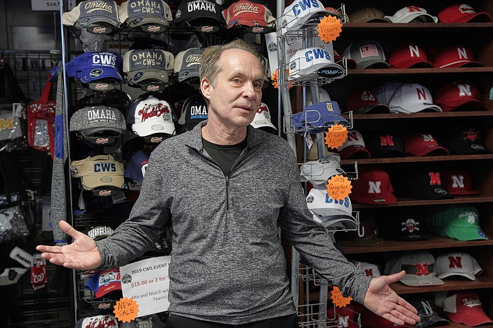 In this March 27, 2020 photo, Rich Tokheim, owner of the Dugout, gestures in front of College World Series articles, in Omaha, Neb. Tokheim's sports apparel shop is directly across the street from the main entrance to TD Ameritrade Park, and more than half his annual revenue comes over the 10 days of the College World Series each June. The Division I baseball championship, decided in Omaha for the past 70 years, is among the many sporting events canceled or postponed because of the coronavirus pandemic. (Nati Harnik/AP)
