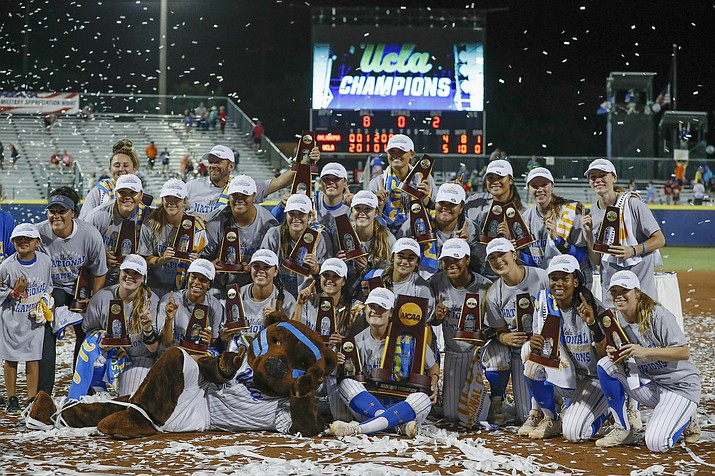In this June 4, 2019, file photo, the UCLA team poses for photos after defeating Oklahoma in the NCAA softball Women's College World Series in Oklahoma City. Smaller cities and communities are dealing with the cancellation of showcase sporting events. For Oklahoma City, that means losing the Women's College World Series. The annual event determines the NCAA softball championship. It has been hosted by Oklahoma City every year but one since 1990. Last year, it brought in an estimated $14 million to the city and its businesses. (Alonzo Adams/AP, file)