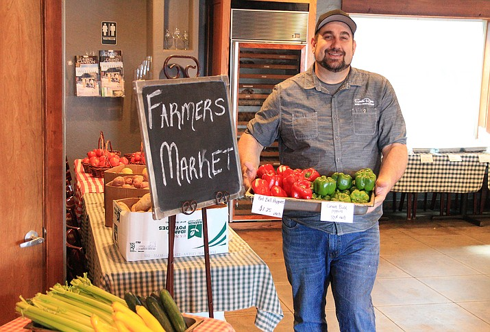 Greg Cole displays produce on sale at the new South Rim's farmers market April 9. The market is open Tuesdays, Fridays and Saturdays. (Loretta McKenny/WGCN)