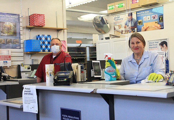 Kent Boyack and Robynn Eckel continue to serve customers at the Williams Post Office as they stay behind sneeze screens and wear personal protective gear April 8. (Loretta McKenney/WGCN)