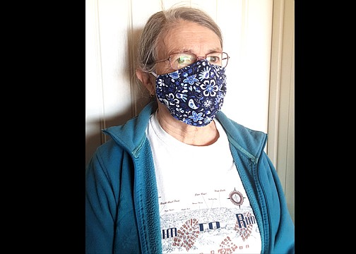 Ann Scott demonstrates the use of one of her homemade masks. (Photo courtesy of Ann Scott)