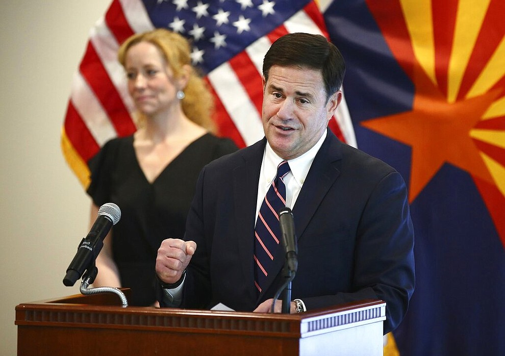 Arizona Gov. Doug Ducey and Arizona Department of Health Services Director Dr. Cara Christ give an update on the COVID-19 pandemic response Tuesday, April 14, 2020 during a news conference at the Arizona Commerce Authority in Phoenix. (Rob Schumacher/The Arizona Republic via AP, Pool)