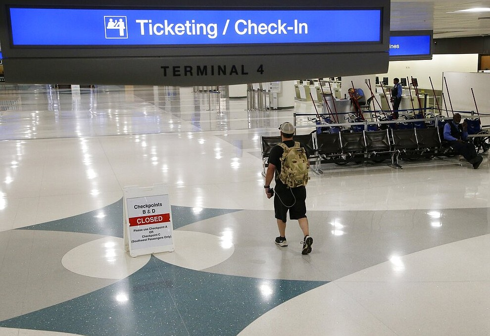 A lone passenger walks to check in at a desolate Phoenix Sky Harbor International Airport Tuesday, April 14, 2020, in Phoenix. The coronavirus has caused a significant decrease in air travel. (AP Photo/Ross D. Franklin)