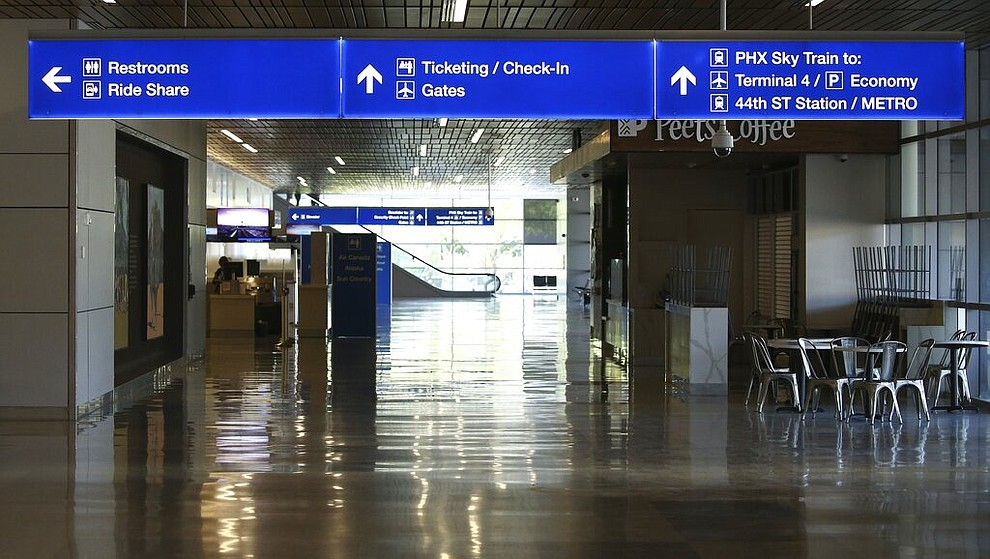 An empty hallway leads to the baggage claim area at Phoenix Sky Harbor International Airport on Tuesday, April 14, 2020, in Phoenix. The coronavirus outbreak has caused a significant decrease in air travel. (AP Photo/Ross D. Franklin)