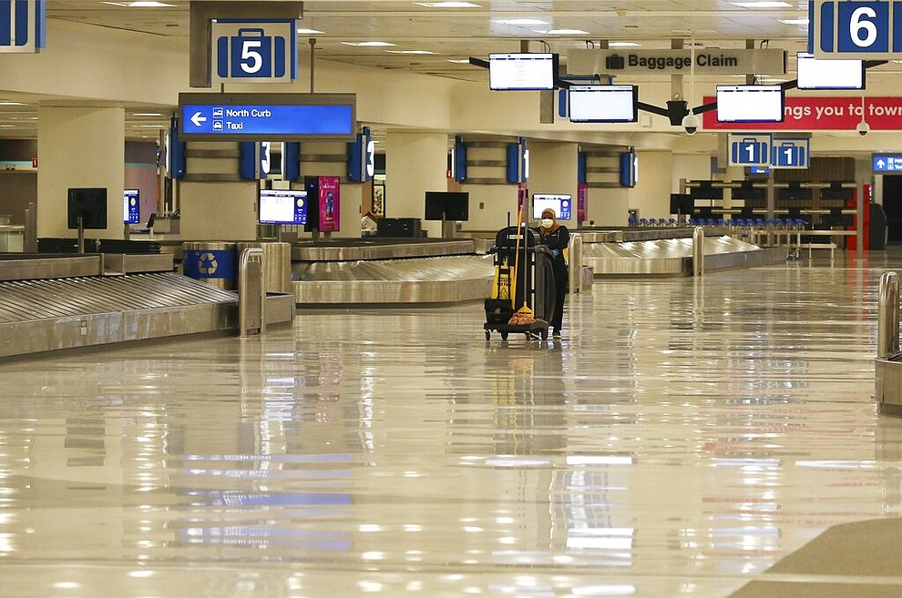 A member of the cleaning crew pushes a cart through an empty baggage claim area at Phoenix Sky Harbor International Airport on Tuesday, April 14, 2020, in Phoenix. The coronavirus outbreak has caused a significant decrease in air travel. (AP Photo/Ross D. Franklin)