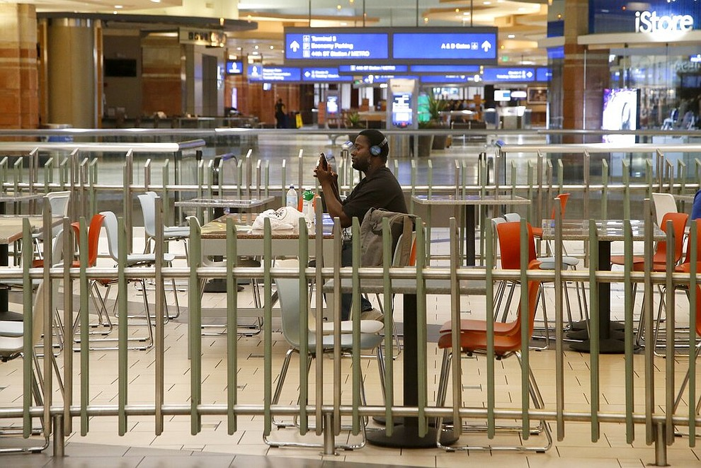 A lone passenger sits in an otherwise empty food court at Phoenix Sky Harbor International Airport on Tuesday, April 14, 2020, in Phoenix. The coronavirus outbreak has caused a significant decrease in air travel. (AP Photo/Ross D. Franklin)