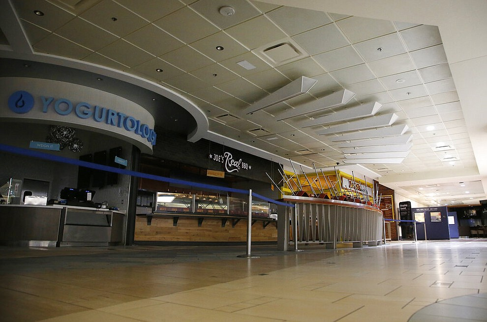 Closed restaurants are cordoned off at Phoenix Sky Harbor International Airport on Tuesday, April 14, 2020, in Phoenix. The coronavirus outbreak has caused a significant decrease in air travel. (AP Photo/Ross D. Franklin)