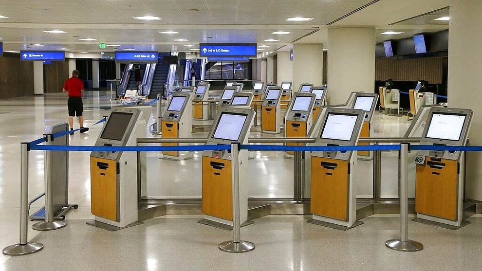 American Airlines check-in kiosks are cordoned off at Phoenix Sky Harbor International Airport on Tuesday, April 14, 2020, in Phoenix. The coronavirus outbreak has caused a significant decrease in air travel. (AP Photo/Ross D. Franklin)