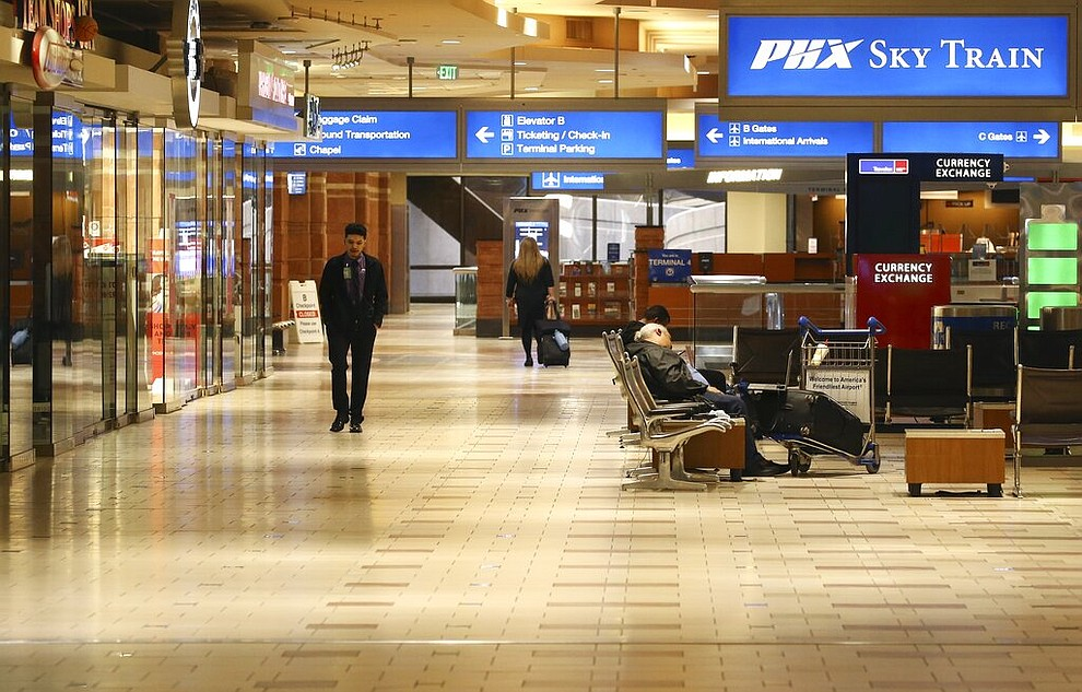 A nearly empty terminal shows few passengers at Phoenix Sky Harbor International Airport Tuesday, April 14, 2020, in Phoenix. The coronavirus has caused a significant decrease in air travel. (AP Photo/Ross D. Franklin)