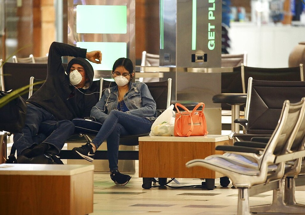 Two passengers wearing face coverings wait for a flight at Phoenix Sky Harbor International Airport on Tuesday, April 14, 2020, in Phoenix. The coronavirus outbreak has caused a significant decrease in air travel. (AP Photo/Ross D. Franklin)