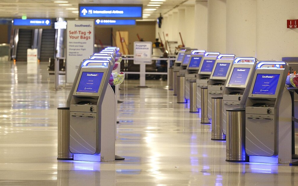 An empty Southwest Airlines check-in area is shown at Phoenix Sky Harbor International Airport Tuesday, April 14, 2020, in Phoenix. The coronavirus has caused a significant decrease in air travel. (AP Photo/Ross D. Franklin)